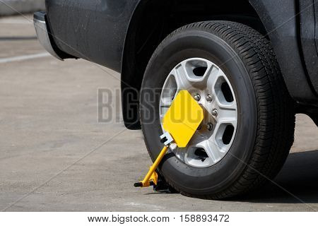 yellow wheel clamp locked in park illegally parked car