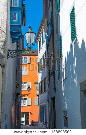 Part of narrow street in the city Zurich. Switzerland. Vintage lantern. Hanging balcony wooden shutters.
