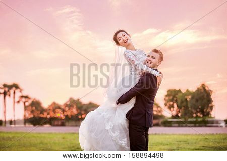 Side view portrait of happy bridegroom carrying bride on field during sunset