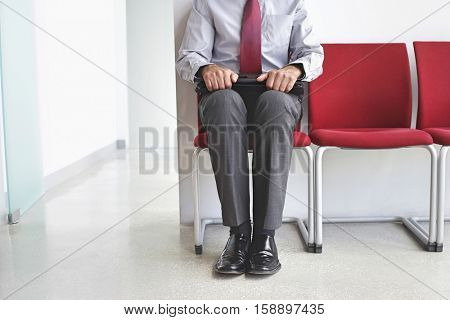 Lowsection of a male executive sitting with laptop on chair in corridor