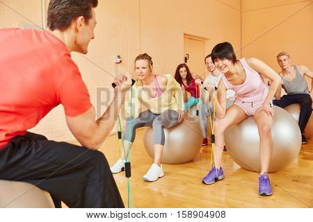 Trainer showing healthy exercise with expanding band in pilates class