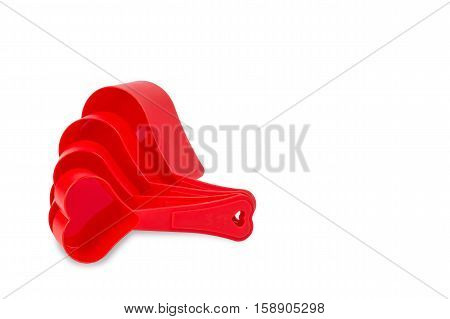 Red heart shape measuring cup isolated on white background