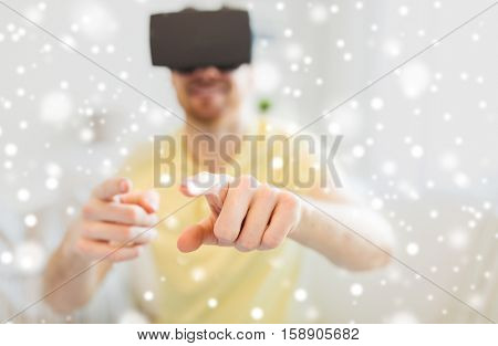 technology, augmented reality, winter, christmas and people concept - close up of happy young man with virtual headset or 3d glasses playing game at home over snow