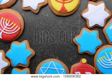 Tasty glazed cookies for Hanukkah on dark grunge background