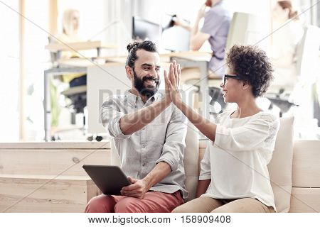 business, startup, gesture, success and people concept - happy creative team with tablet pc computer making high five in office
