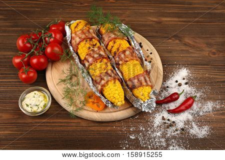Grilled corns with beacon on wooden cutting board