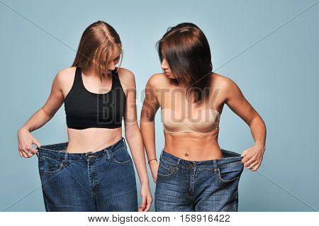 Two Fit Young Woman In Loose Jeans