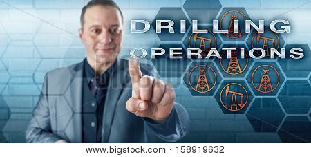 Smiling male industrial manager pressing DRILLING OPERATIONS on a virtual control screen. Petroleum industry concept and fossil fuel metaphor for drilling technology derrick pumpjack and oil wells.