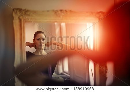 Girl putting on her necklace