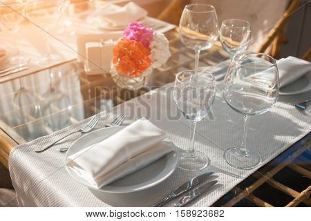 Table with wineglasses and plates. Tableware and sunlight. Invite your family for breakfast. How to create perfect cleanliness.