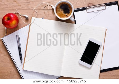 Notepad, diary and mobile with espresso coffee. Office supplies and business devices on modern wooden office desk. Working table top view. Education or job background with copy space on paper sheet