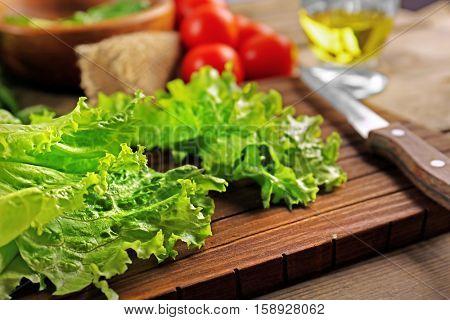 Fresh lettuce leaves for vegetable salad on cutting board