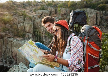 Smiling adventure couple with map on slope. look at map