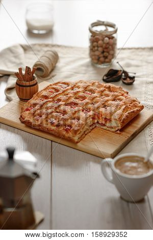 peach pie with a cup of cappuccino coffee maker on a wooden table