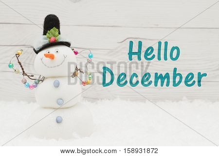 Hello December message Some snow and a snowman on weathered wood with text Hello December