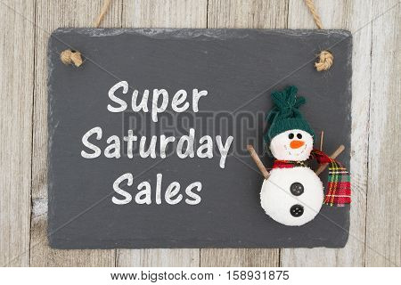 Old fashion Christmas store message A retro chalkboard with a snowman hanging on weathered wood background with text Super Saturday Sale