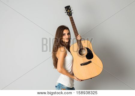 portrait of attractive young girl with guitar in hands posing in studio smiling on camera