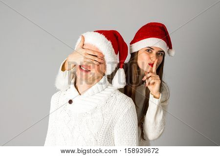 young couple in love celebrates christmas and having fun in santa hats in studio on gray background