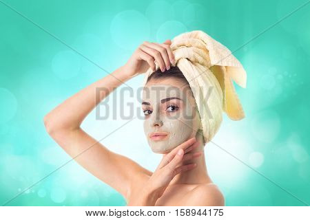 charming Young girl takes care her skin with cleansing mask on face and towel on head isolated on white background. Health care concept. Body care concept. Young woman with healthy skin.
