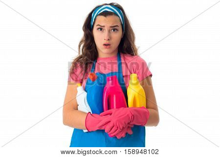 portrait of young sad maid girl in an apron with cleansers isolated on white background