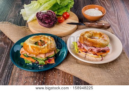 Hearty breakfast sandwich on a bagel with bacon and cheese on a wooden table