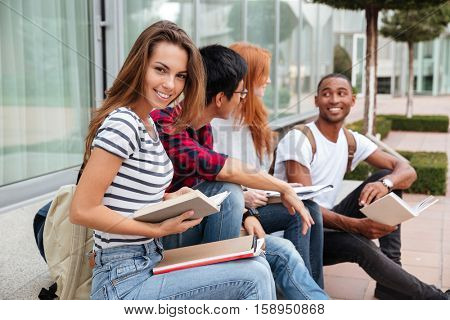 Cheerful pretty young woman sitting and reading book with her friends outdoors