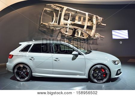 Wolfsburg, Germany - April 15, 2016. Audi RS3 car on display at Audi showroom in Autostadt theme park in Wolfsburg. Side view of the car with body framework hanging above.