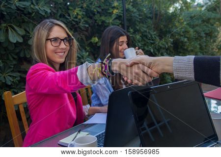 Young businesswomen shaking hands. They are greeted before they start working together.
