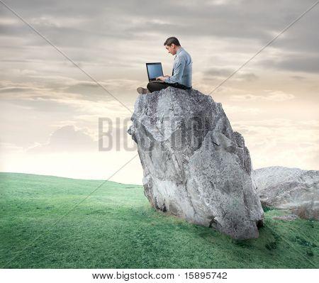Empresário sentada numa rocha e usando um laptop