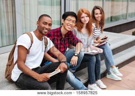 Multiethnic group of cheerful young people sitting outdoors together