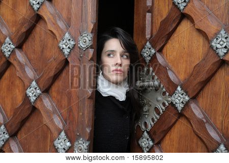 Woman coming out of an ancient door
