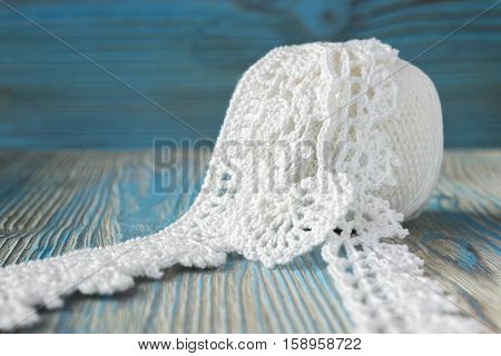 White ball of eco natural cotton yarn for knitting crochet knitted leaves. Rustic wooden background Irish crochet lace pattern elements