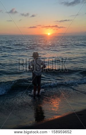 Small boy stands in the waves on the beach at the sundown and pulls up his trousers