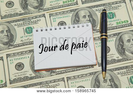 Notebook page with French  text JOUR DE PAIE (PAYDAY) on dollar background