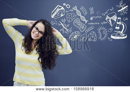 Young smiling woman on blue gray background with biology icons.