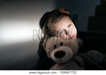 Sad little girl embracing her teddy bear - feels lonely - if you are small girl teddy bear is willing to be your best friend - instagram filter applied