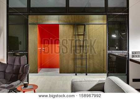 Luminous hall in a loft style with a red entrance door, wooden wardrobes and lockers, ladder with wheels, armchair, table with book and cup, sofa, glass partitions. Parquet and tiles are on the floor.