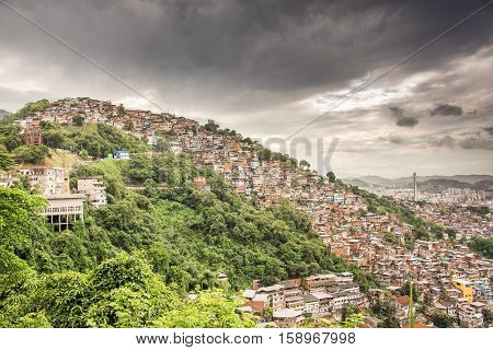 View of Rio de Janeiro Slum, favela Morro dos Prazeres on mountains with dark grey sky, Brazil