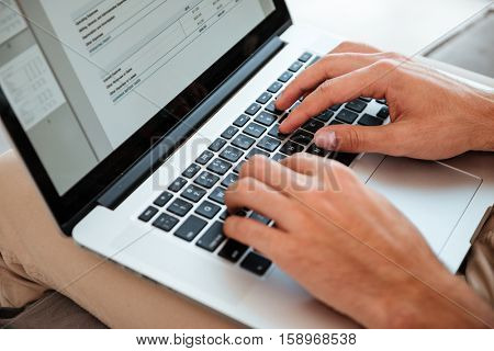 Cropped image of a young man's hands typing on his laptop while man sitting on sofa.