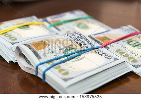 Piles of hundred dollar bills on wooden table