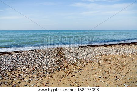 landscape with views of the Baltic Sea, on the banks of large and small stones and sand, wet stripe up water, small waves and endless horizon, blue sky and bright water