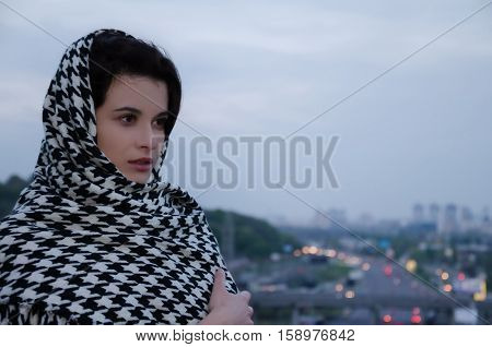 brown-eyed girl with dark hair wearing a scarf against the blue cloudy sky