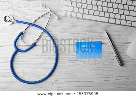 Stethoscope with keyboard and mouse on light wooden background