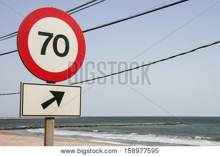 Traffic sign outdoors. Round speed limit road sign on the road beside the sea