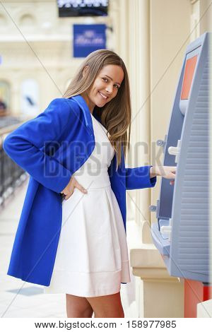 Young brunette woman in blue coat withdrawing money from credit card at ATM