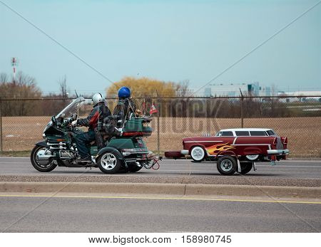 Toronto, Ontario, Apr. 28, 2013, stylish bikers traveling on their motorcycle, tricycle with a small trailer on the road