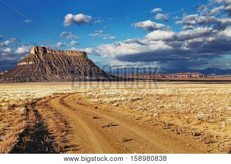 Factory Butte, isolated flat-topped sandstone mountain in Utah desert, USA