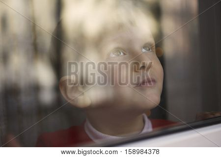 Young boy looking outside through a window