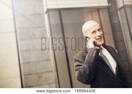 Businessman getting out of the elevator while being on the phone