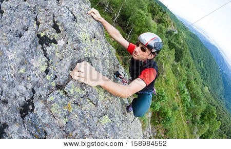 Young man climbing on a wall with green valley on the background. Italian Alps, Europe.